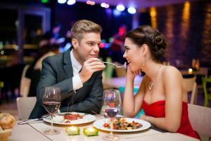 Affectionate couple in restaurant,  him feeding she