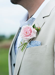The groom wears a carnation on his lapel