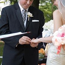The groom slides the ring on the bride's finger