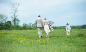 The bride and groom walk through a field