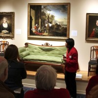 Museum goers look at a painting