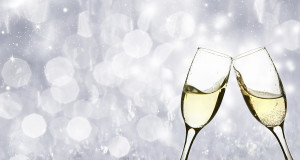 Glasses with champagne against sparkling holiday background