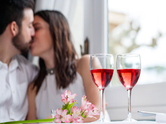 A couple share a kiss and two glasses of wine