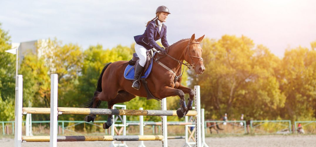 Girl riding horse and jumping at a horse show