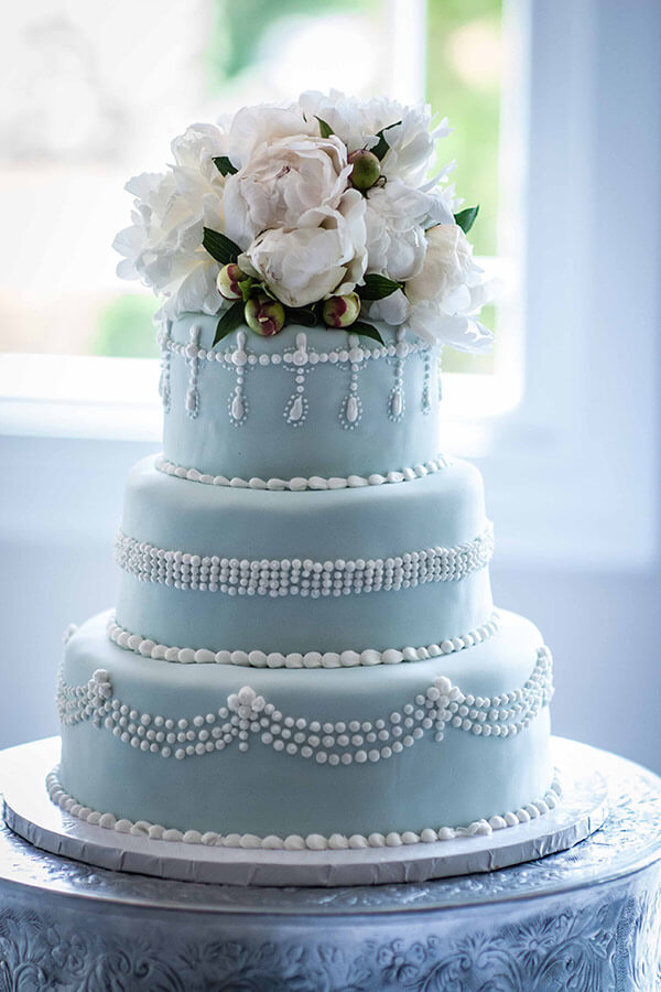 Blue, three tier wedding cake with white flowers on top