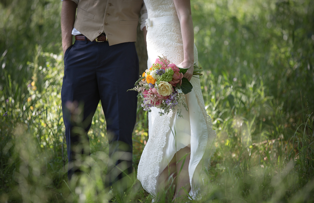 Hipster wedding couple from the wait down to focus on boquet