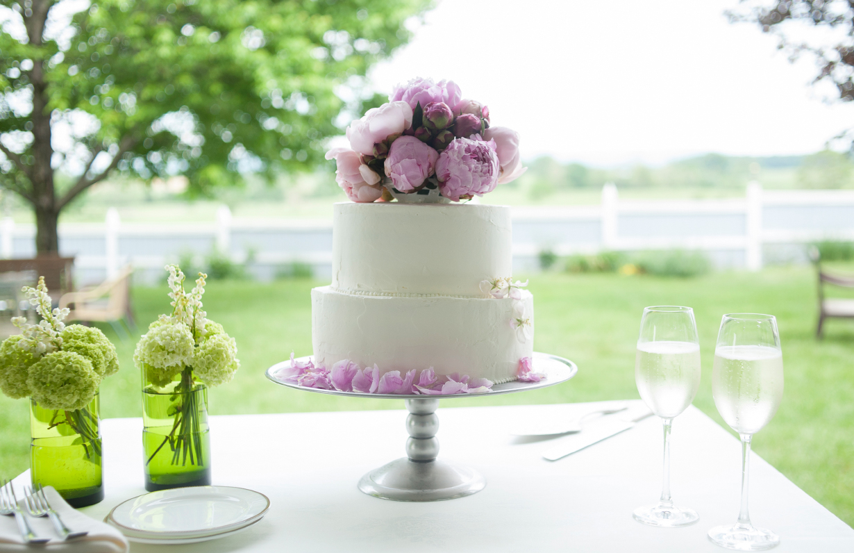 Weddig cake topped with fresh flowers with pastoral view behind