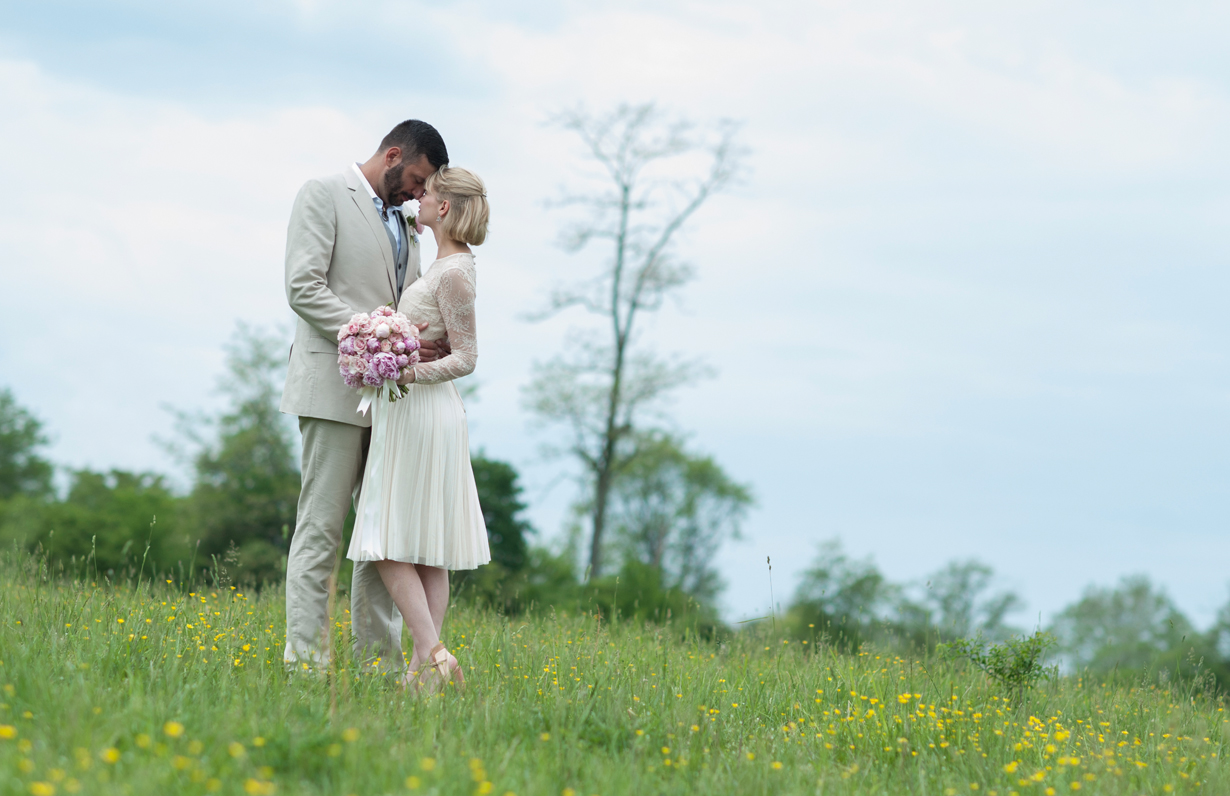 Wedding couple in a field touching foreheads