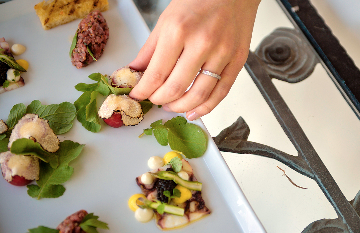 Hand with weding band reaching for gourmet appetizer