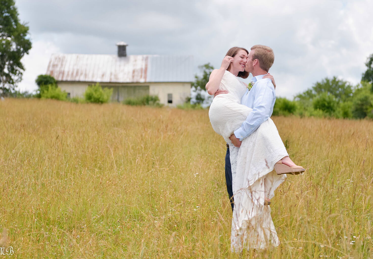 Groom holding his bride in a field at our Northern Virginia wedding venue