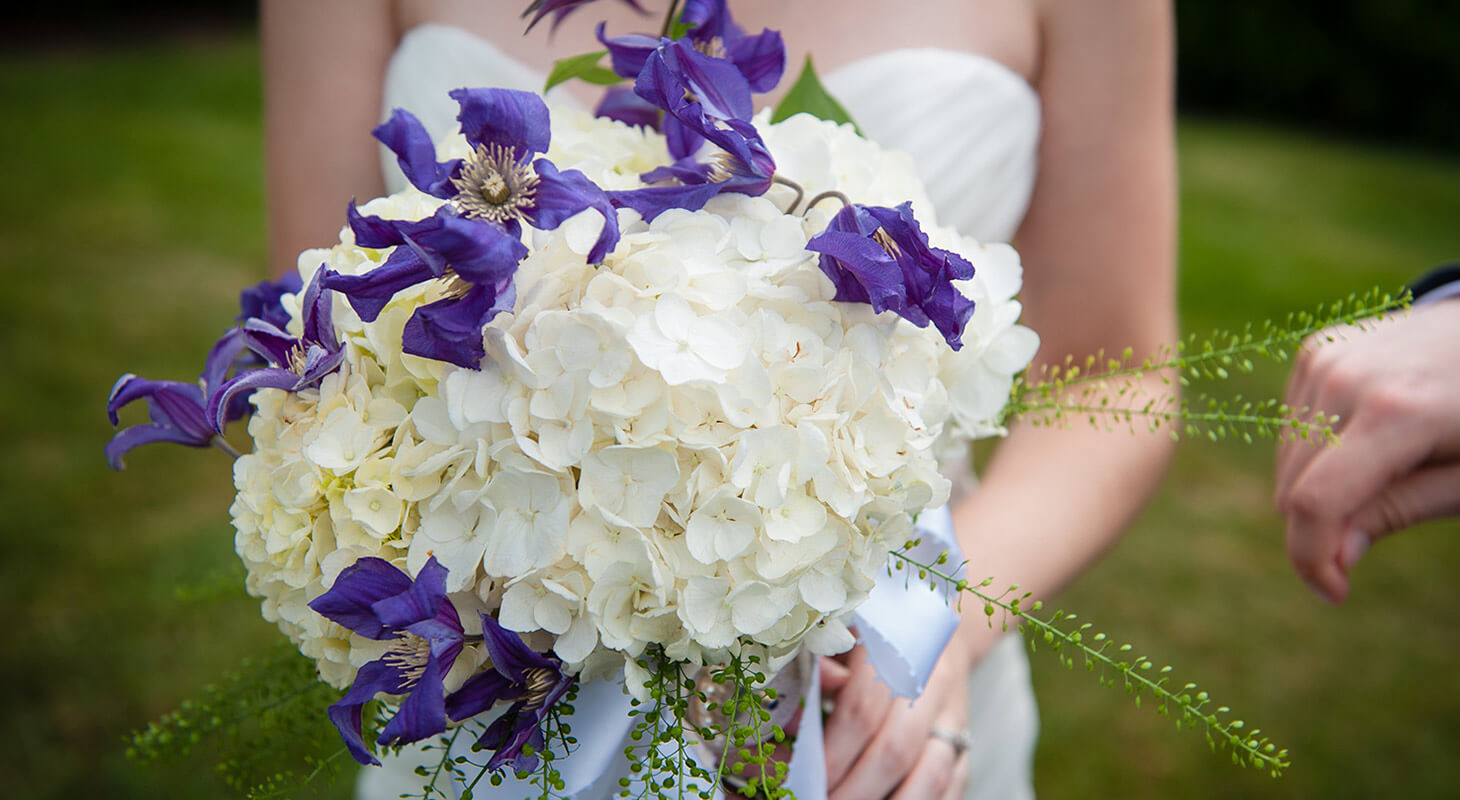 Bride holding a bouquet of purple and white flowers at our Northern Virginia elopement venue
