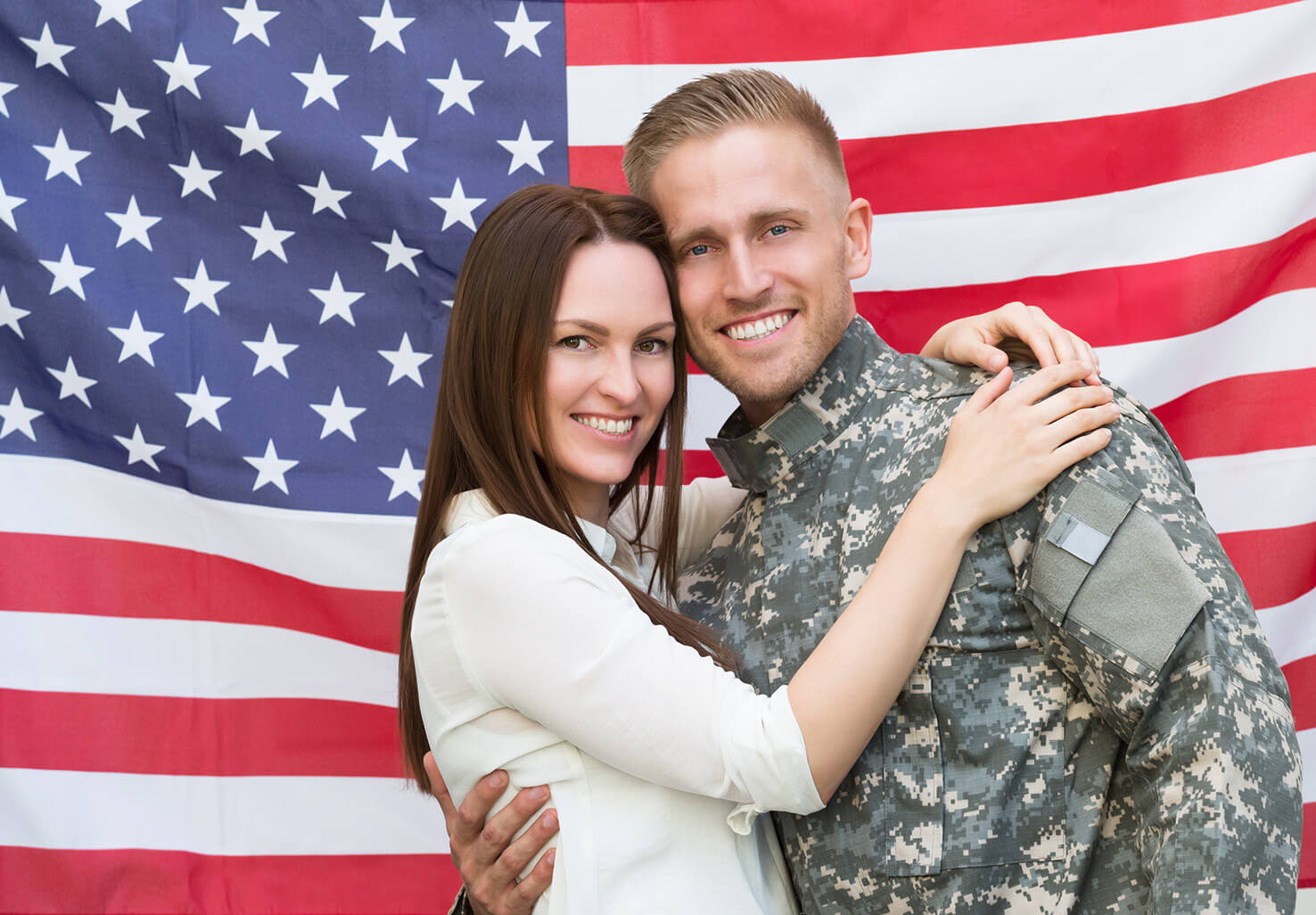 Soldier and his wife in front of an American flag