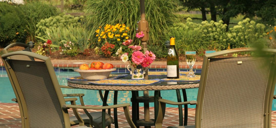 Table by the pool with wine and flowers