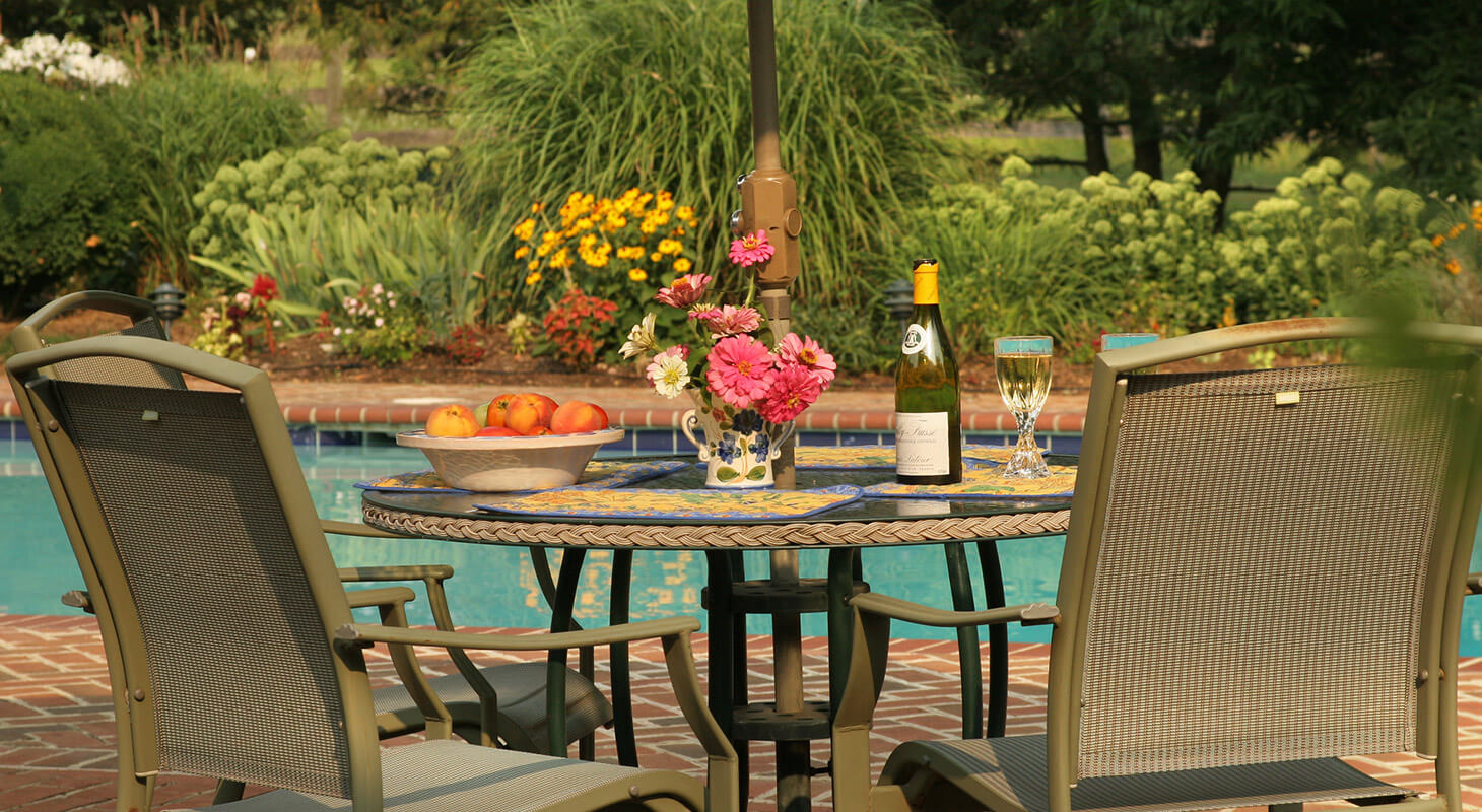 Table by the pool with wine and flowers at our Shenandoah Valley B&B