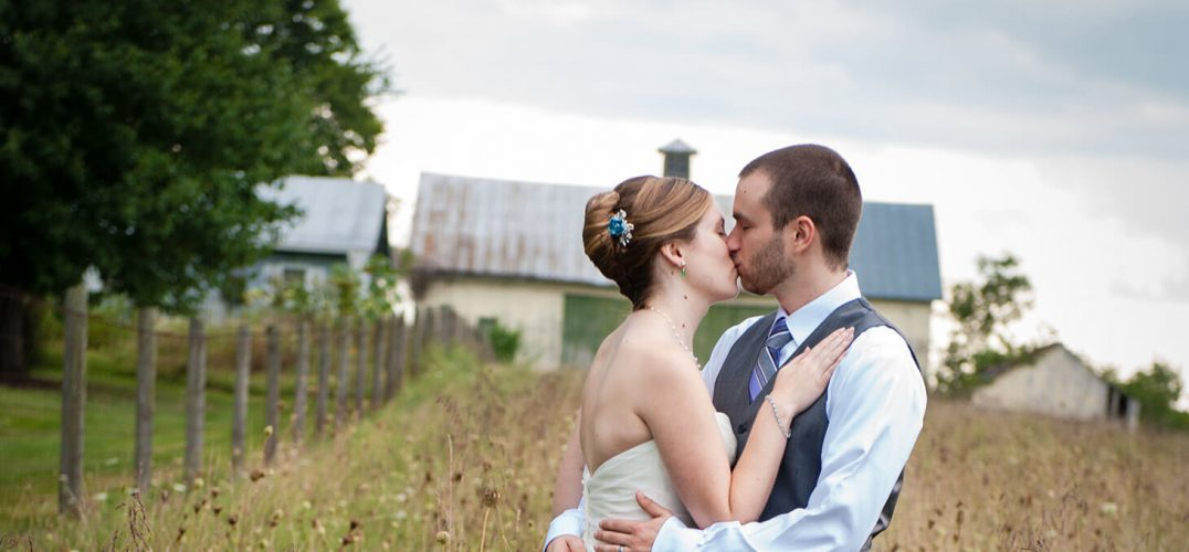 Wedding couple kissing in a field