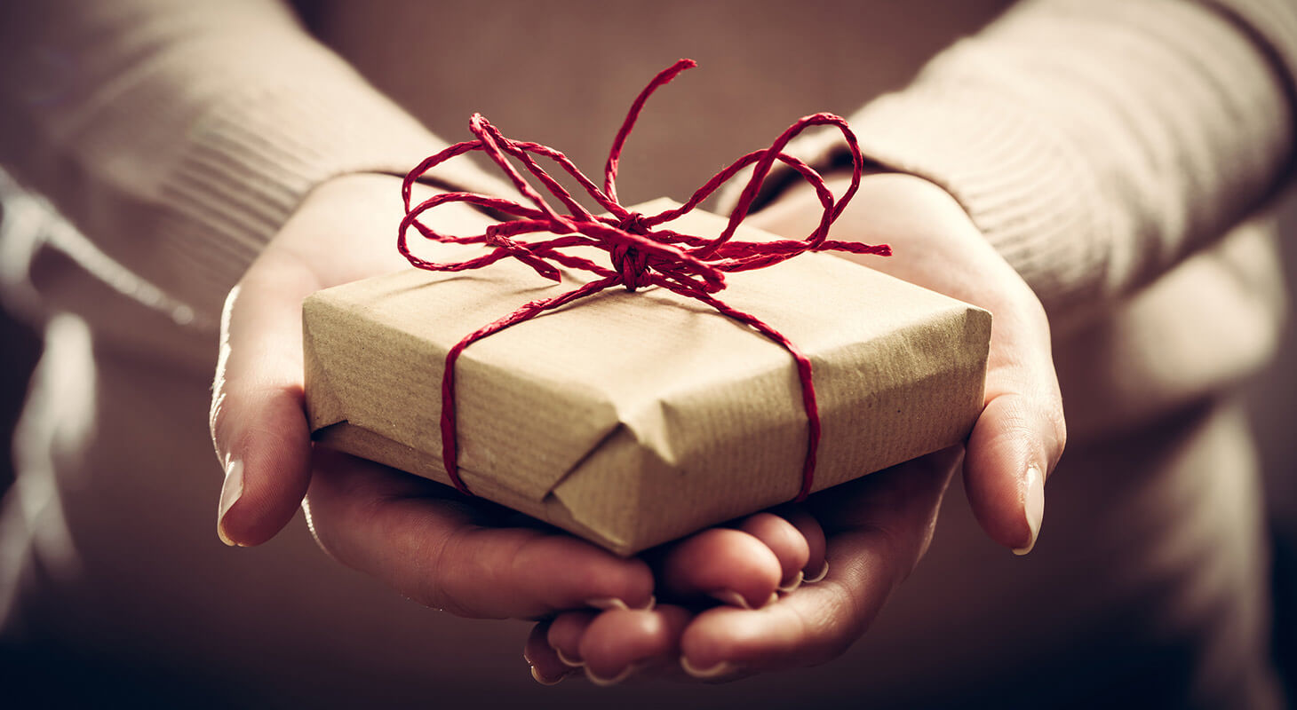 Hands holding a small gift with red ribbon