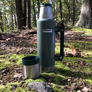 Green Stanley Thermos on a patch of moss in the woods, leaves and stones nearby.