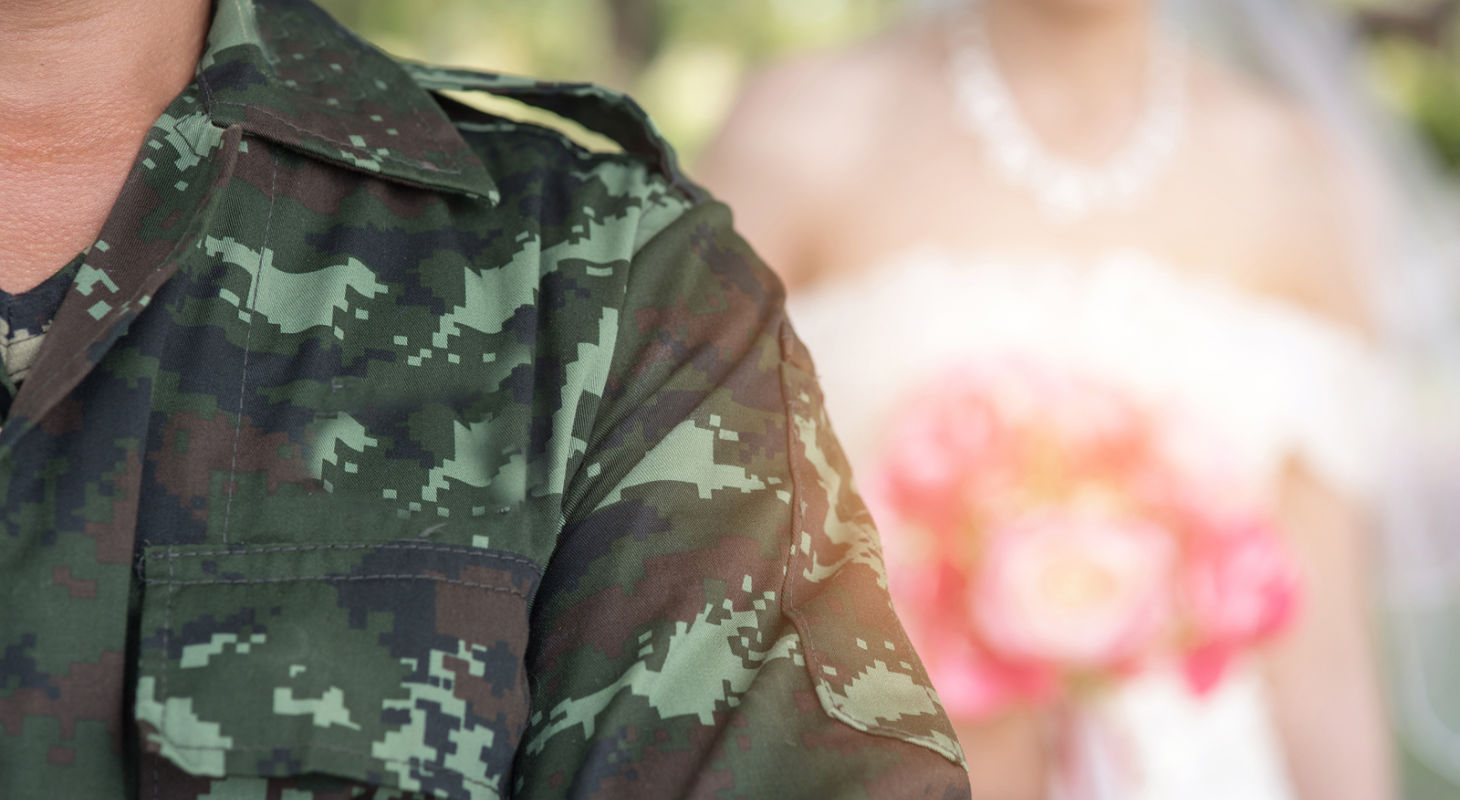 A military figure stands in front and the bride stands behind in a wedding ceremony.