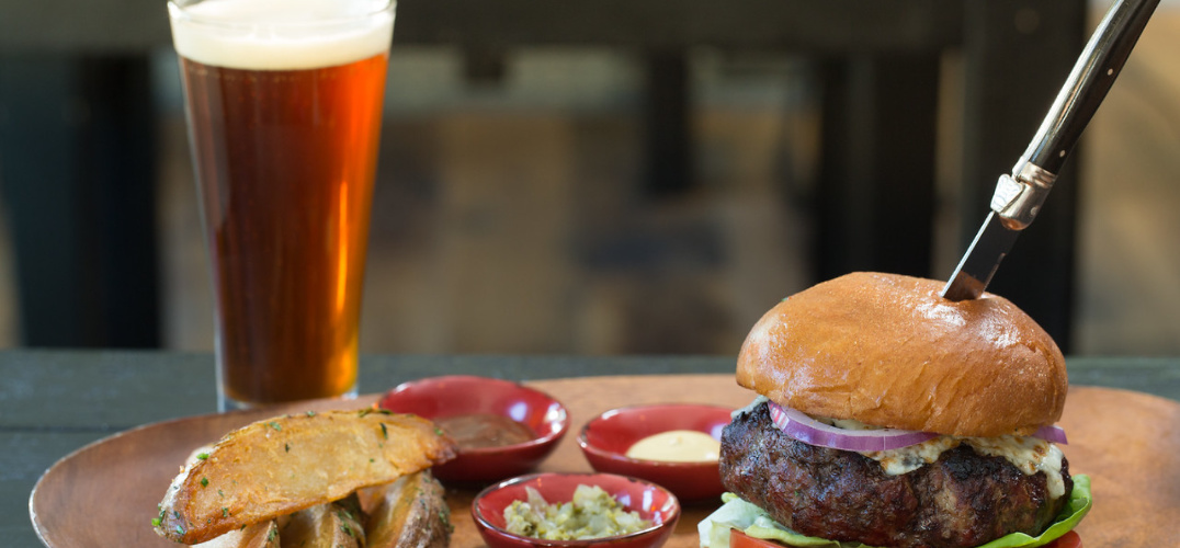 a fancy burger and fries with a glass of beer