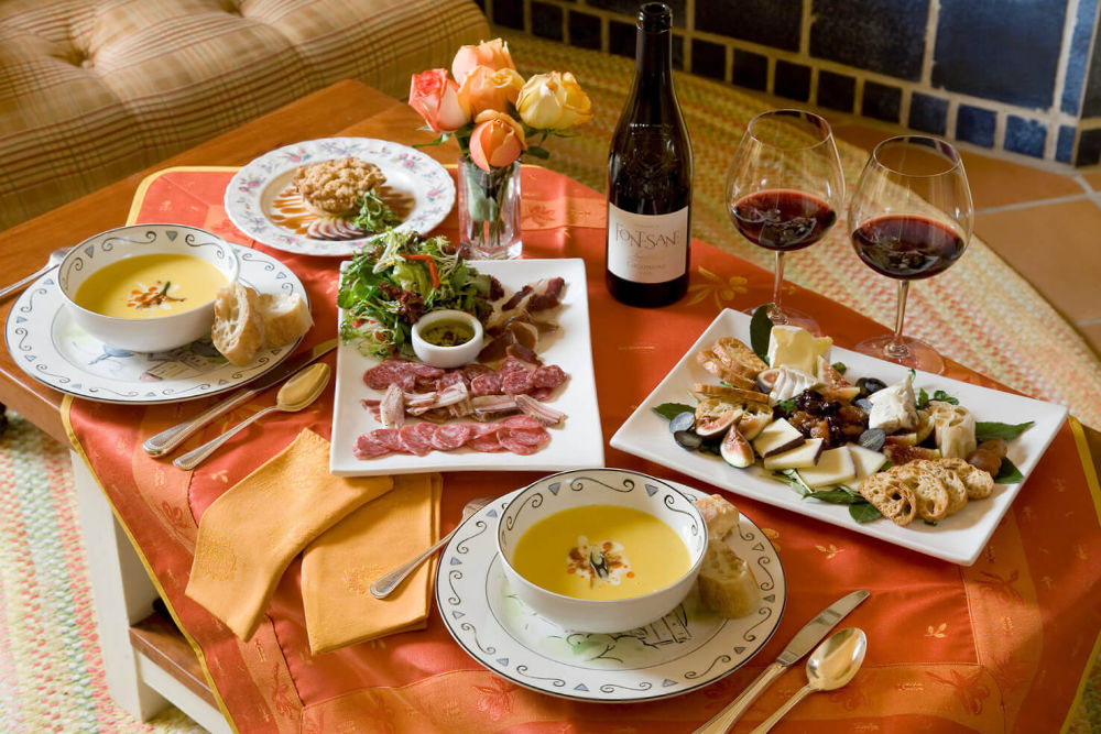 a table full of gourmet food with red wine