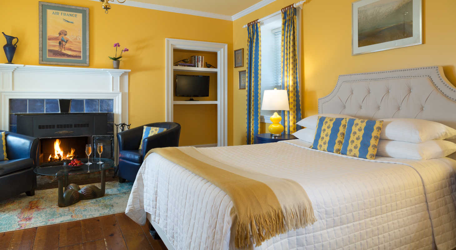 Cozy yellow bedroom with fireplace at L'auberge Bed and Breakfast