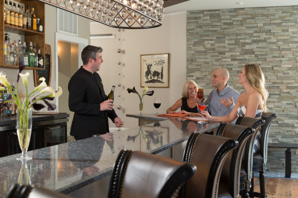 Sommelier Christian Borel pouring wine at the bar for guests of L'Auberge Provencale