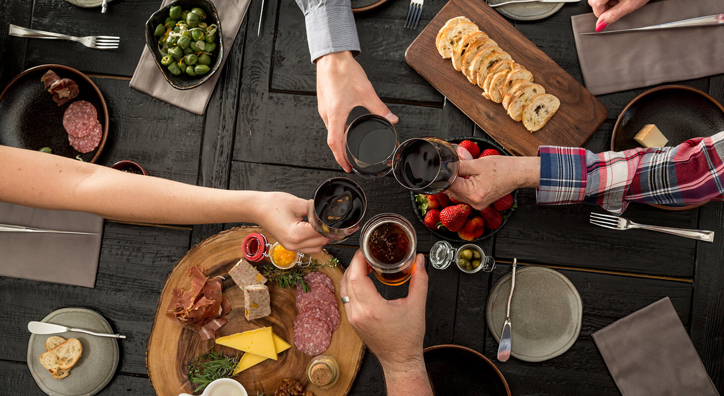 friends toasting with drinks over a table of food