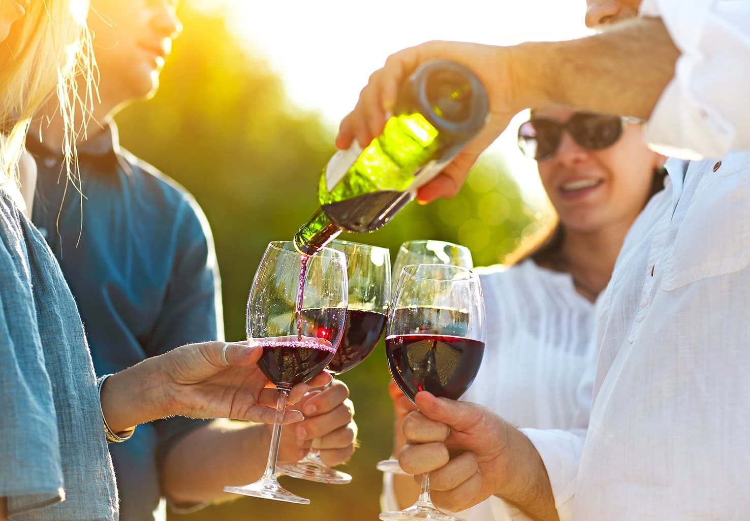 group of people tasting red wine on a sunny day