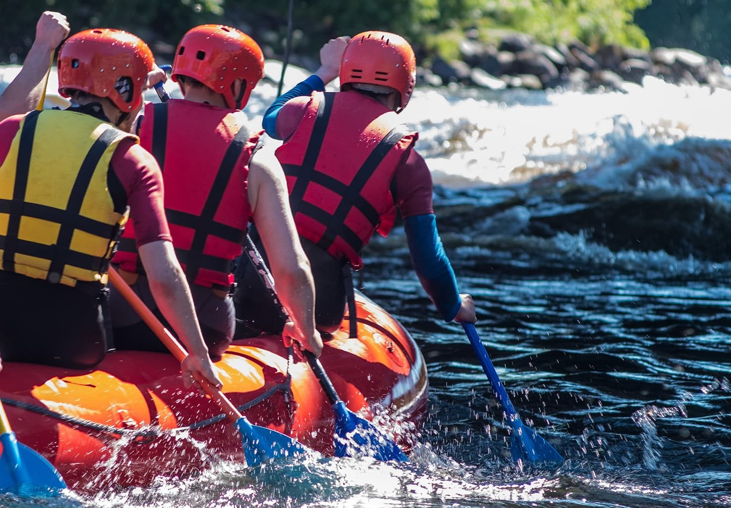 people rafting on a river in the summer