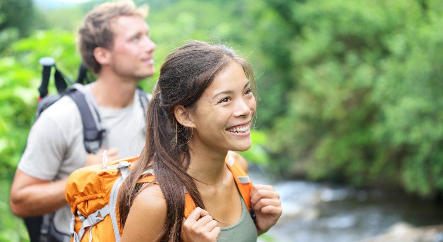 a couple hiking near a river