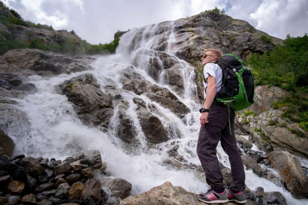 a man hiking near a waterfall
