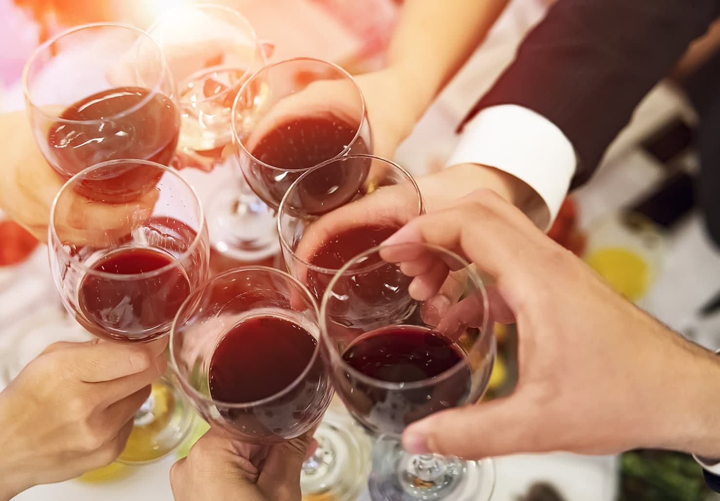 people toasting with wine glasses over dinner