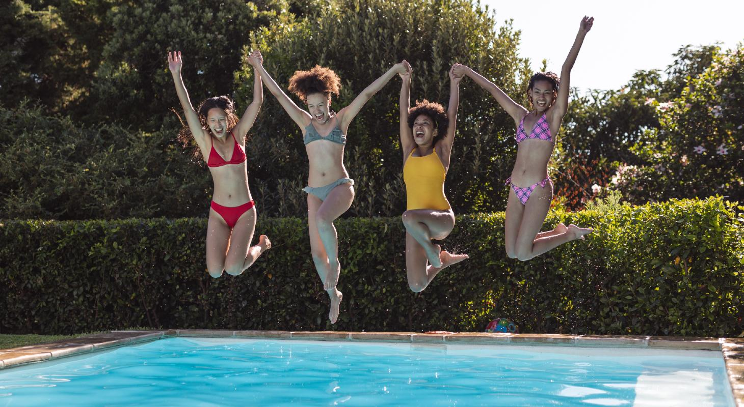 four young women jumping into the pool