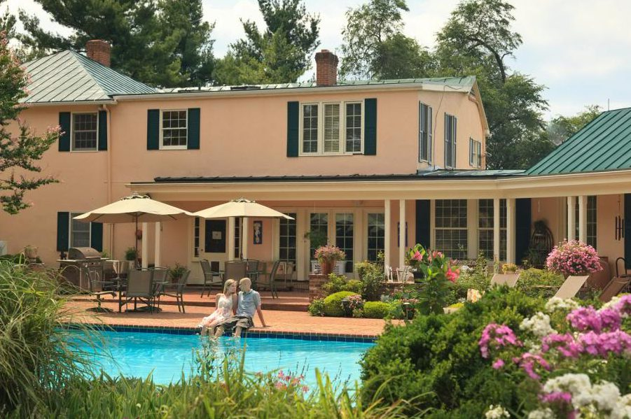 A couple lounging by the pool on a Virginia wellness getaway