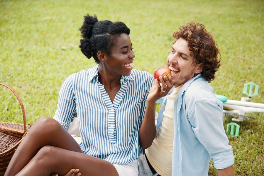 a man and woman eating an apple on a picnic